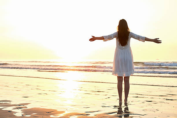woman standing arms outstretched on beach during sunset - beyaz elbise stok fotoğraflar ve resimler