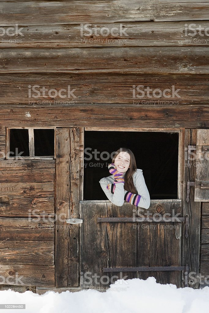 Woman standing at barn door stock photo