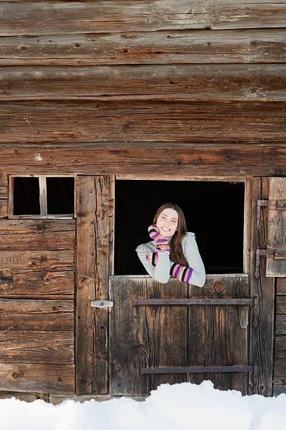 Woman standing at barn door stock photo
