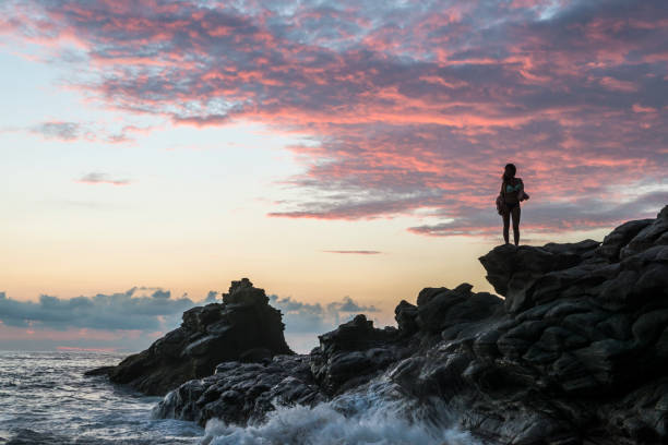 woman standing at beach during dramatic sunset in mexico - rocky coastline stock pictures, royalty-free photos & images