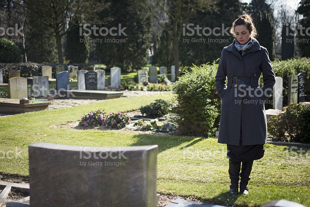 Woman standing at grave stock photo
