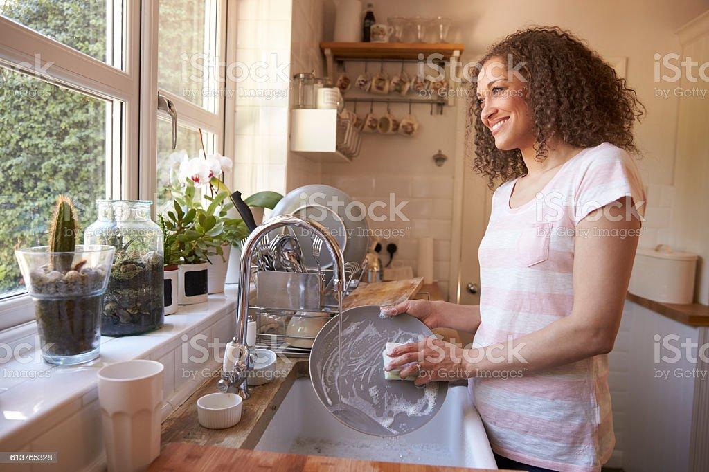 Woman Standing At Kitchen Sink Washing Up stock photo