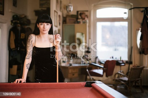 Young tattooed woman standing at pool table looking at camera.