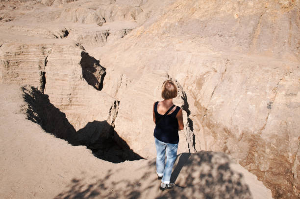 Woman standing at the edge of a precipice stock photo