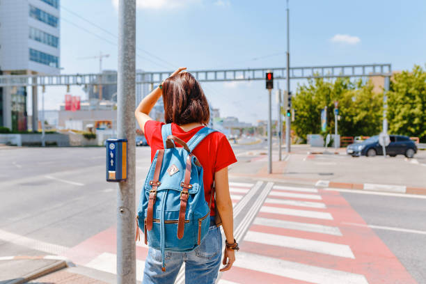 woman standing at the zebra crossing and traffic light - singapore nature stock photos and pictures