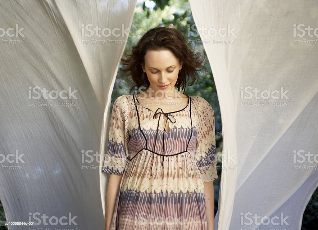 Woman standing at washing line, smiling, eyes closed royalty-free stock photo