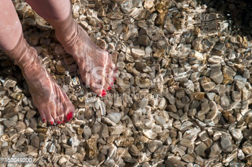 522909925 istock photo woman standing barefoot in clear sea water 152049200