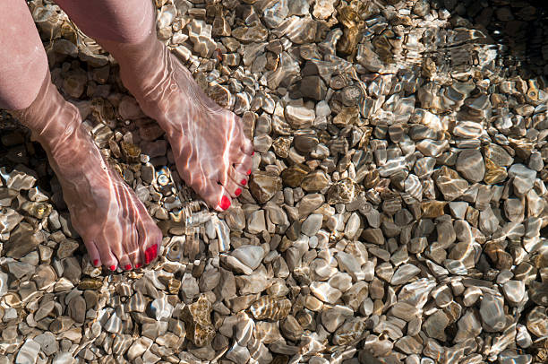 woman standing barefoot in clear sea water stock photo