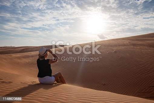 istock Woman standing barefoot on the dune in the desert 1148620689