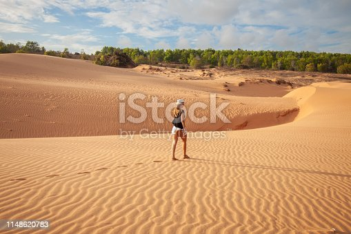 istock Woman standing barefoot on the dune in the desert 1148620783