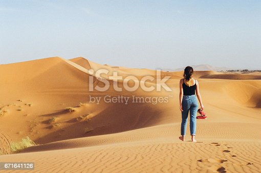 istock Woman standing barefoot on the dune in the desert 671641126