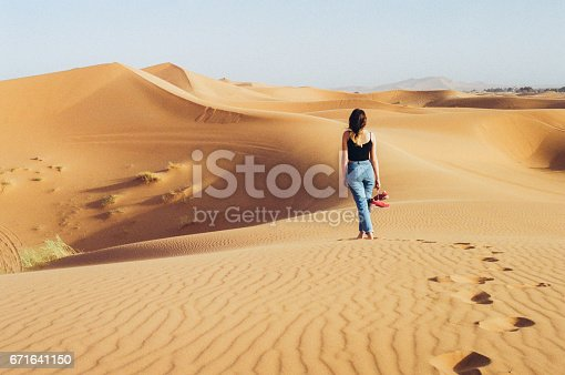 istock Woman standing barefoot on the dune in the desert 671641150