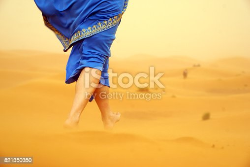istock Woman standing barefoot on the dune in the desert 821350350
