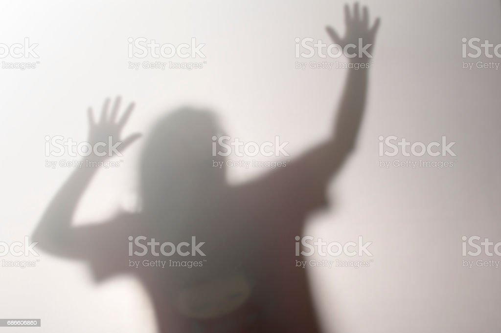 Woman standing behind frosted glass.image creates feeling of depression,Behind a screen,Blurry shadow royalty-free stock photo
