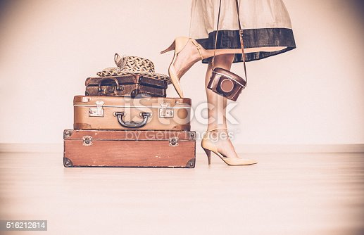 Woman standing with her vintage suitcases inside a home concept symbolizing she is going away on a trip or going on a vacation. Woman is  wearing a beige dress and shoes. She is holding a vintage camera. Only showing the woman's legs, hands and shoes. Horizontal sepia image. Copy space.
