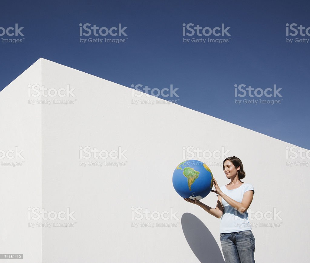 Woman standing beside wall with globe royalty-free stock photo