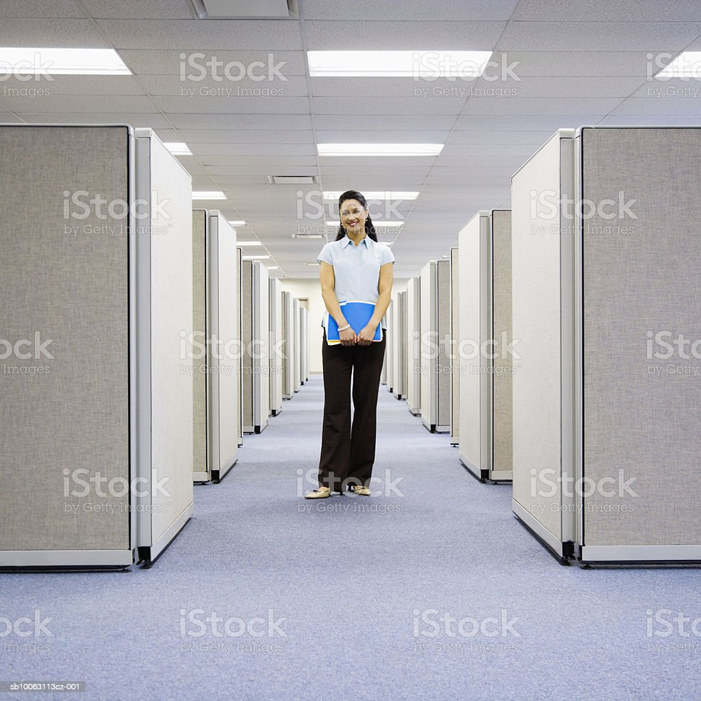Woman standing between office cubicles, holding file, smiling foto de stock libre de derechos