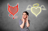 istock Woman standing between the angel and devil hearts 1300130012