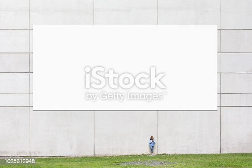 A woman using her phone by a wall with a large blank billboard in a city environment.