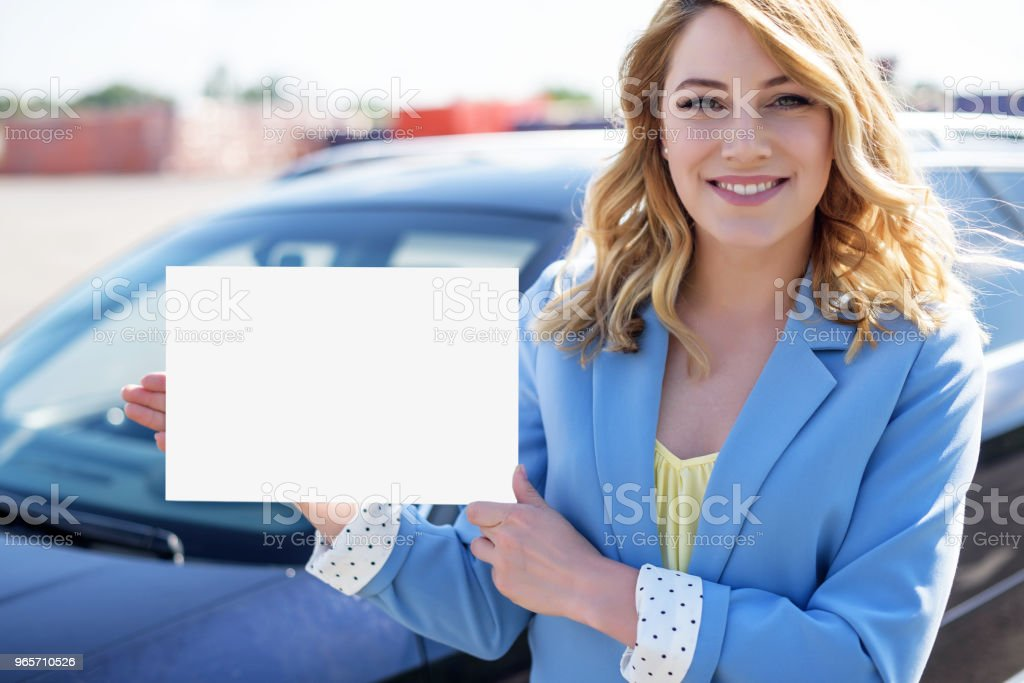 Woman standing by car holding a white blank poster - Royalty-free Adult Stock Photo