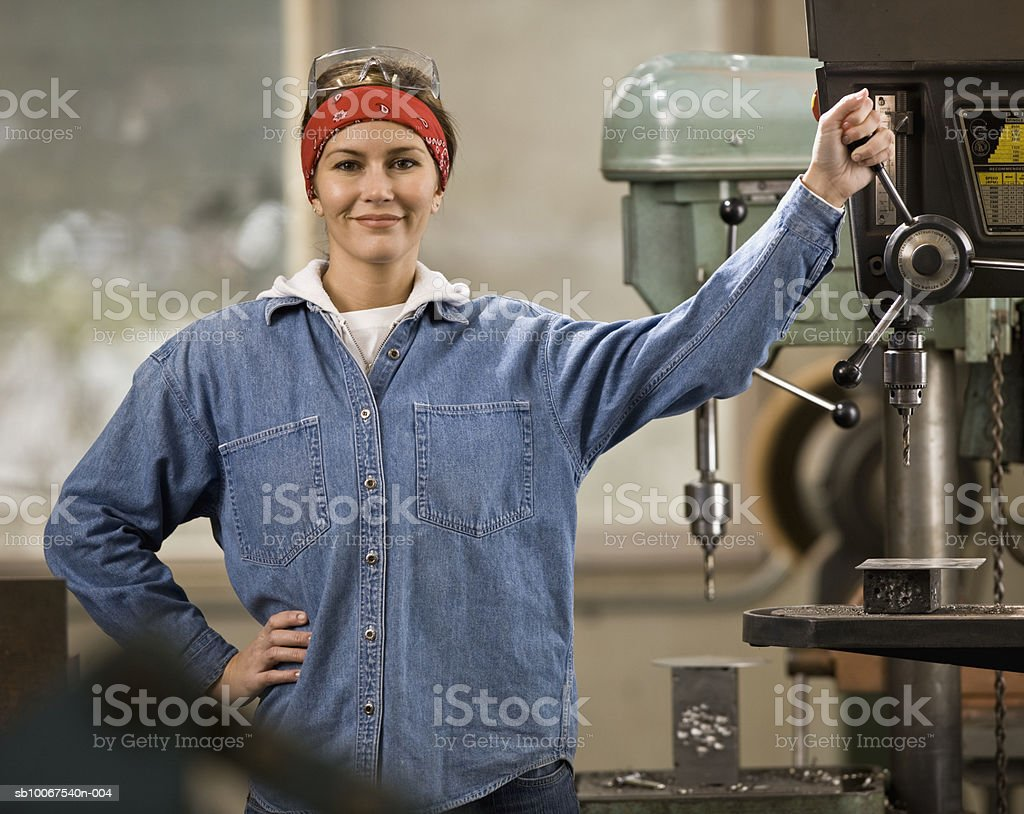 Woman standing by drill machine, smiling, portrait royalty-free stock photo