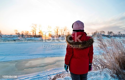 Woman standing by the lakeside in winter.