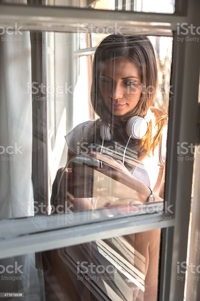 Woman standing by the window and listnening to music stock photo