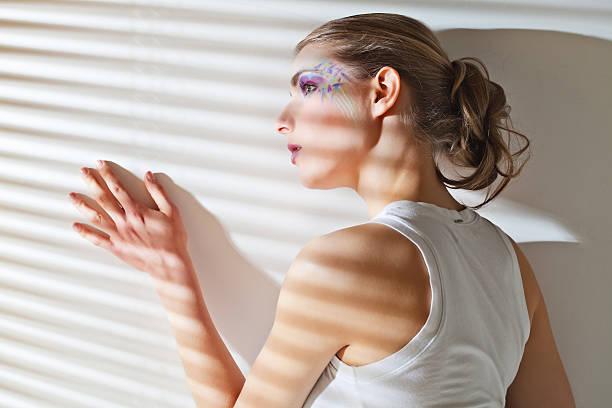 femme debout près de la fenêtre avec stores - cosmetique store photos et images de collection