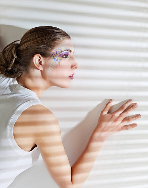 Woman standing by the window with blinds stock photo
