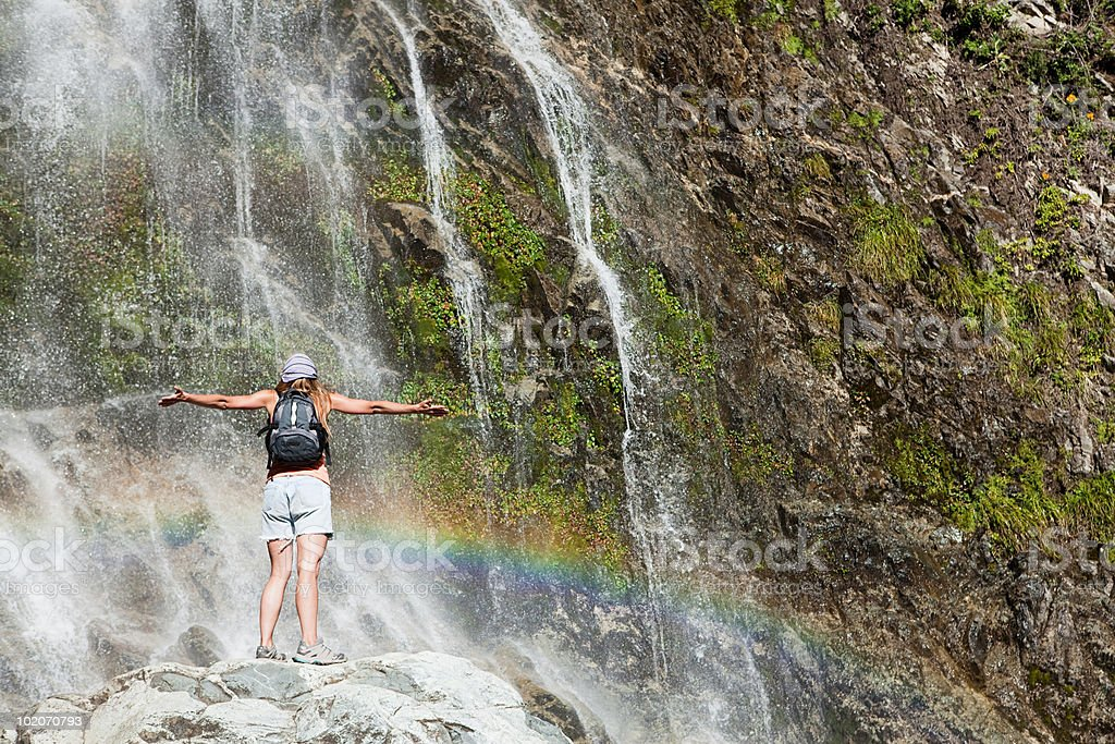 Woman standing by waterfall with arms open royalty-free stock photo