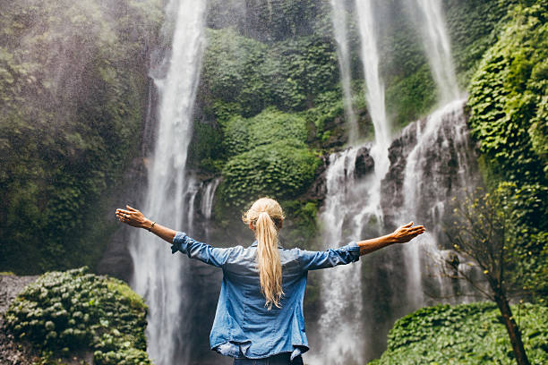 woman standing by waterfall with her hands raised - beauty in nature stock photos and pictures