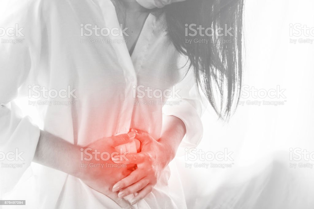 woman standing hand touching her stomach pain during period stock photo