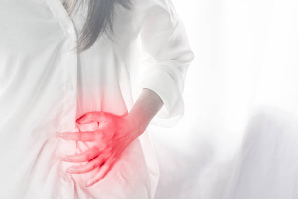 woman standing hand touching her stomach pain during period - cyst stock pictures, royalty-free photos & images