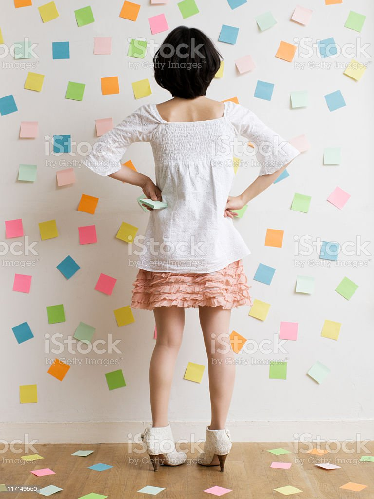 Woman Standing in a Room of Sticky Notes royalty-free stock photo
