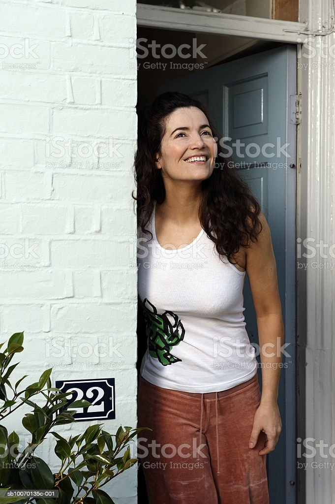 Woman standing in doorway and smiling royalty-free stock photo