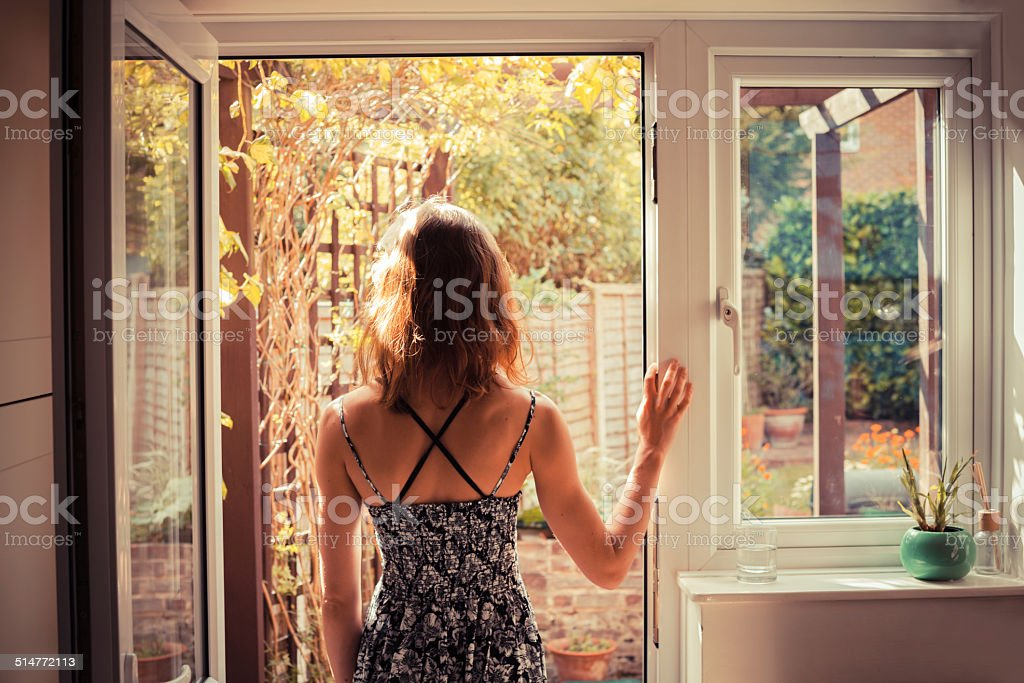 Woman standing in doorway at sunrise stock photo