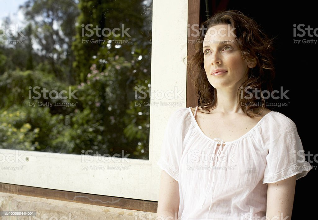 Woman standing in doorway, smiling royalty free stockfoto
