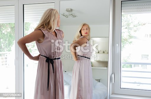 istock Woman standing in dress in front of mirror 1027250030