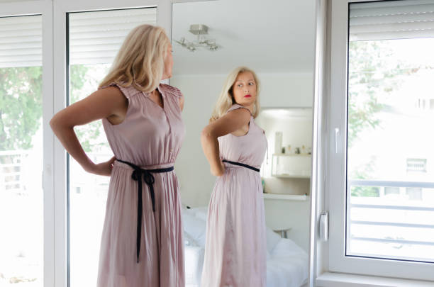 woman standing in dress in front of mirror - woman mirror foto e immagini stock