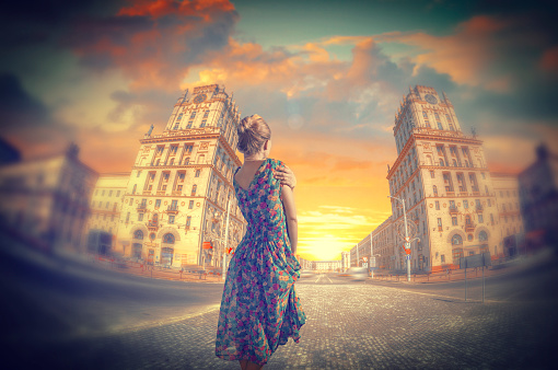 woman standing in dress. Two towers on Railway station square City Gates Minsk Belarus