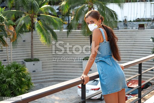 A woman standing in front of a fence. Girl in a mask at home in quarantine. High quality photo