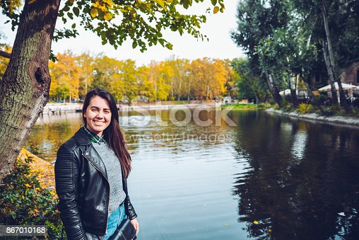 istock woman standing in front of lake in warm autumn weather 867010168