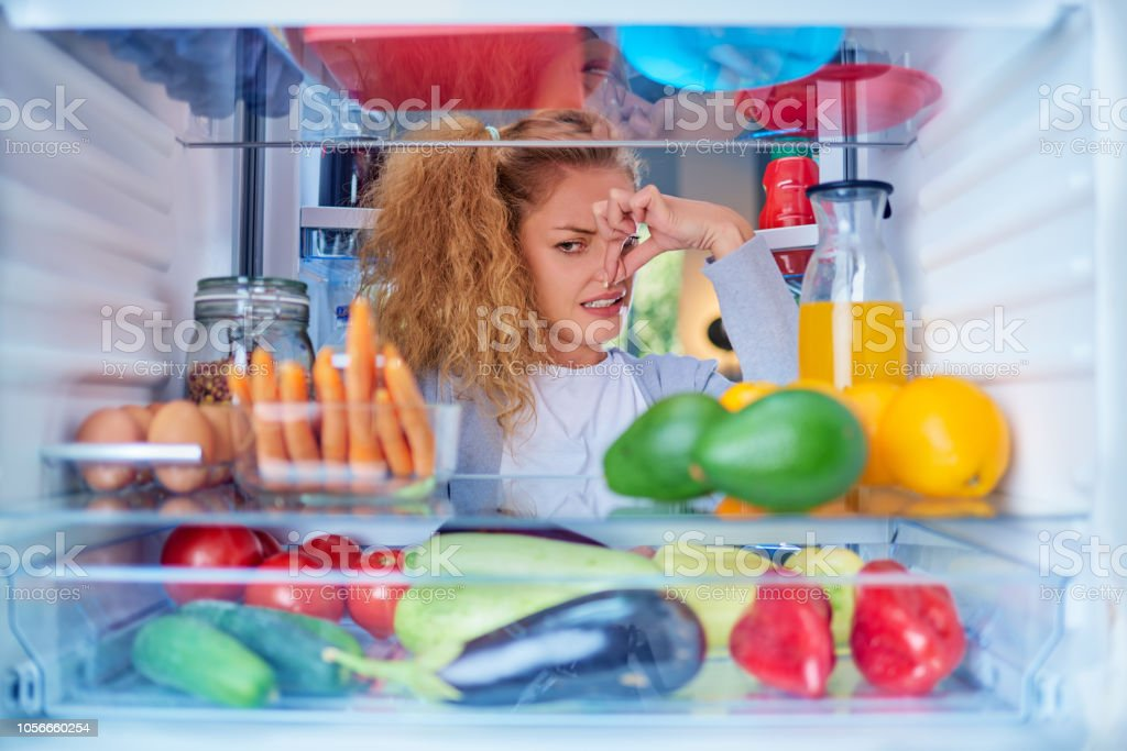 Woman standing in front of opened fridge and holding up to her nose...