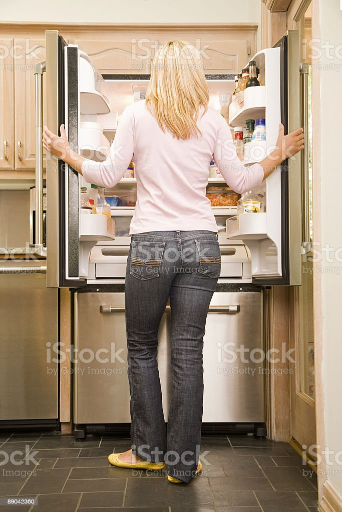 Woman Standing in Front of Refrigerator in Kitchen royalty-free stock photo