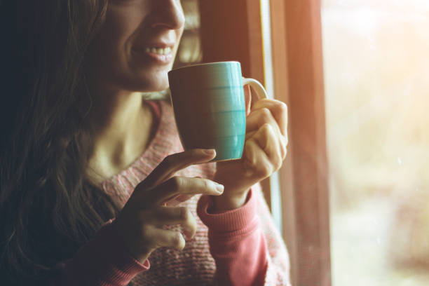 woman standing in front of window and drinking coffee - tea hot drink stock photos and pictures
