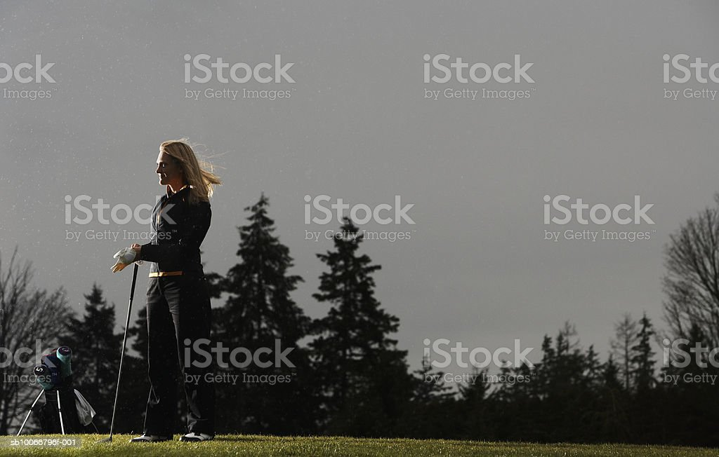 Woman standing in golf course, side view royalty-free stock photo