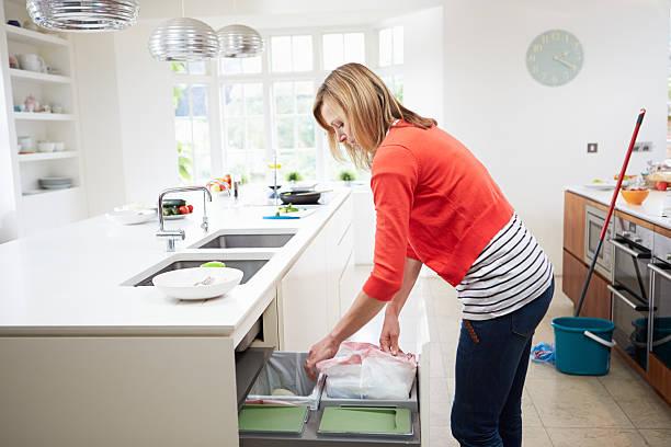 Woman Standing In Kitchen Emptying Waste Bin stock photo