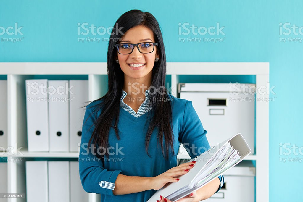 Woman standing in office with folder stock photo