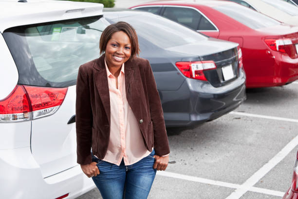 Woman standing in parking lot stock photo