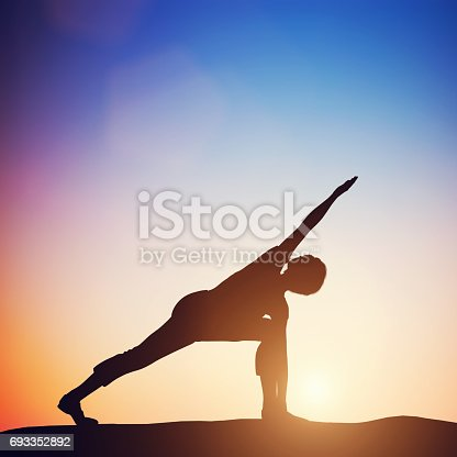 Woman standing in revolved side angle yoga pose meditating at sunset. Zen, meditation, peace